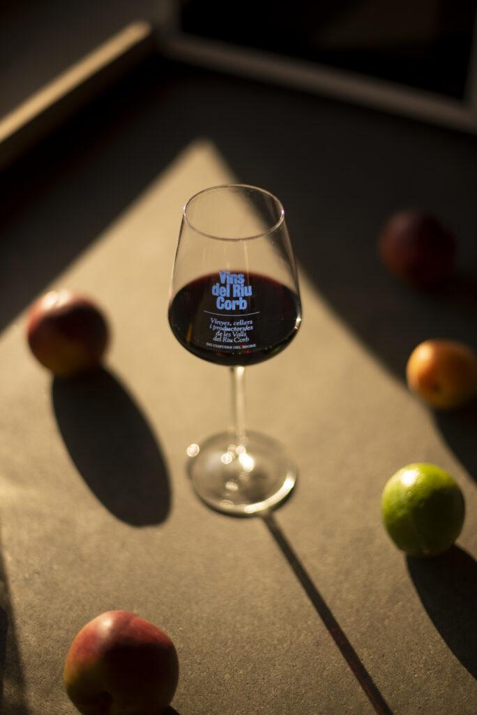 Imatge on es veu una copa de vi negre damunt d'una taula on hi ha fruites i verdures típiques de les terres de ponent.