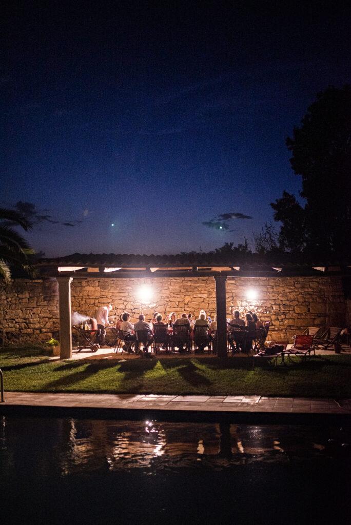 Imatge on es veu gent gaudint d'una cata de vins i una barbacoa en un vespre d'estiu.