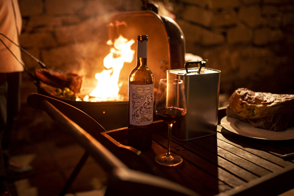 Imatge d'una barbacoa on es pot veure com s'està cuinant una peça de carn d'un kilo i mig i al seu costat hi ha una ampolla de Mercès i oli d'oliva extra verge del Molí Duran.