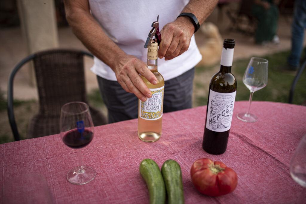 Imatge d'un client destapant i obrint una ampolla de vi del nostre celler.
