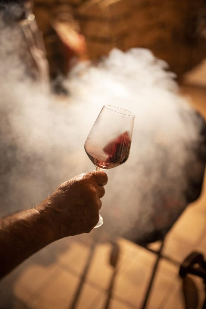 Imatge on es pot veure algú tastant un vi amb una barbacoa al costat.